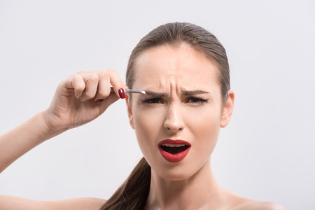 Young woman is tweezing her eyebrow with pain. She is standing and looking at camera with frustration. Isolated
