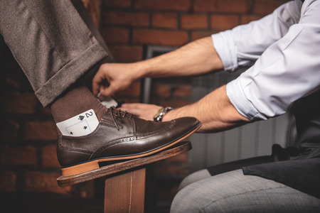 footware: worker inserting the playing cards into the shoes to protect socks of a client, side view