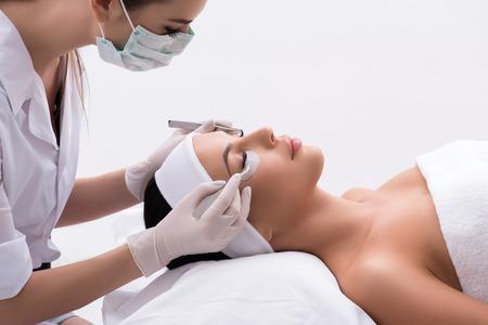 巧みな美容師は、濃度を持つクライアントに対して人工まつげを作っています。彼女は彼女の目の近くにピンセットを保持しています。若い女性は