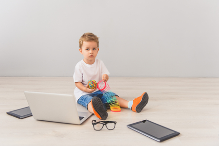Little cute boy sitting on floor in studio, posing for camera next to digital gadgets Imagens