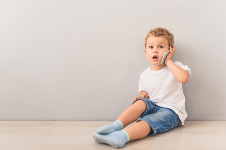 Shot of happy young boy talking on cellphone while sitting on floor in studio
