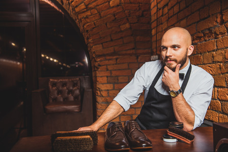 footware: thoughtful bearded craftsman sitting at the desk with brogues and brushes Stock Photo