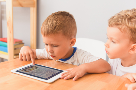 Entertaining themselves with technology. Cropped shot of two cute boys sitting at desk and using digital tablet, playing at home