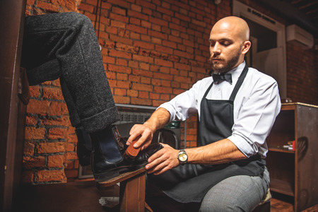 brogues: bald worker brushing brogues of a man who sitting in front of him
