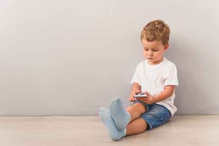 Shot of cute small boy playing with smartphone while sitting on floor against of gray wall on background