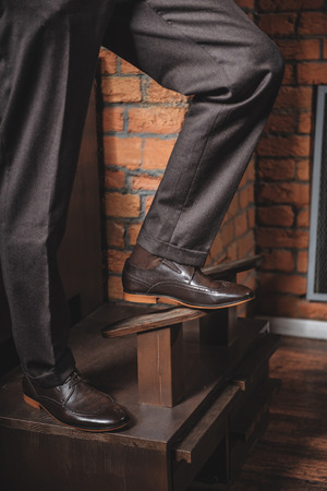 waxed legs: legs of a man standing on a wood retro stand station in waxed shoes
