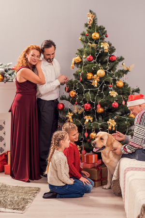 decorate: Happy family is celebrating New Year at home. Man and woman are standing near fir-tree and embracing. Kids and grandfather are playing with dog