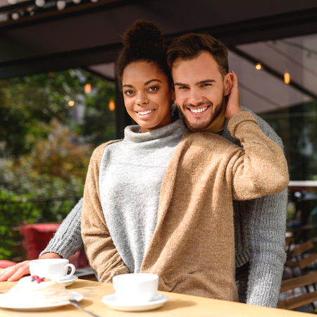 portrait of a cheery couple standing in front of a table with breakfast, selective focus Stock Photo