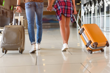Close up of legs of young man and woman walking at airport with suitcases. They are holding hands