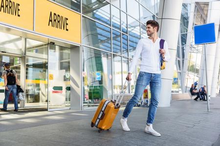 De gelukkige jonge man kwam van reis aan. Hij loopt van het vliegveld met bagage en lacht. Guy kijkt terug en lacht Stockfoto