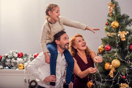 Glückliche Familie hängt Spielwaren auf Weihnachtsbaum mit Freude. Vater hält Mädchen auf seinen Schultern. Vater steht und lächelt