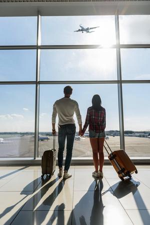 젊은 남자와여자가보고 항공기 비행 하 고 꿈을. 그들은 공항에 서서 여행 가방을 들고있다. 스톡 콘텐츠