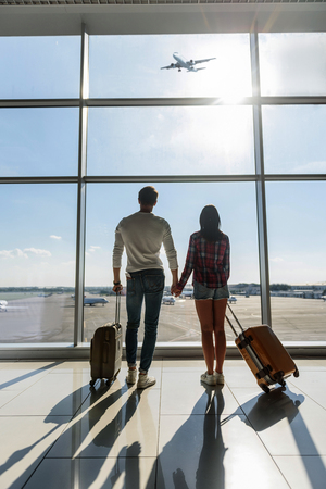 Young man and woman are watching aircraft flight and dreaming. They are standing in airport and holding suitcases
