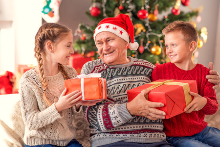 Happy old man is celebrating Christmas with kids. They are sitting on couch at home and embracing. Boy and girl are holding gifts and smiling Stock Photo