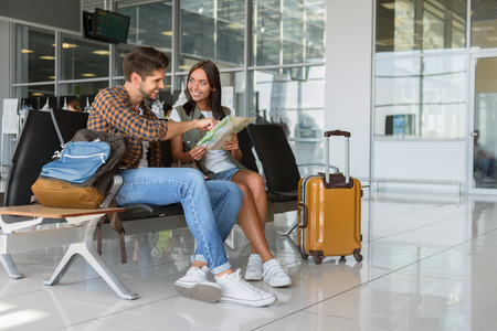 幸せな若いカップルは、スーツケースの近くの空港に座っています。地図が読めると笑みを浮かべています。