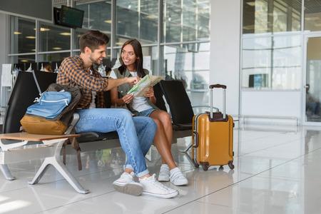 Feliz pareja de jóvenes está sentado en el aeropuerto cerca de la maleta. Ellos están leyendo mapa y sonriente Foto de archivo - 65153274