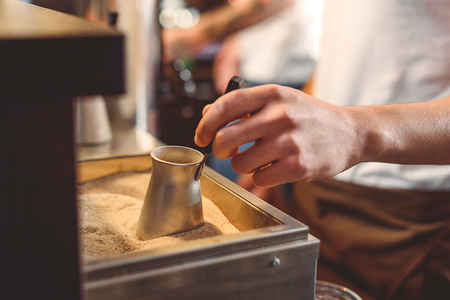 adding sugar: hand of a barman adding sugar to a coffee from the table Stock Photo