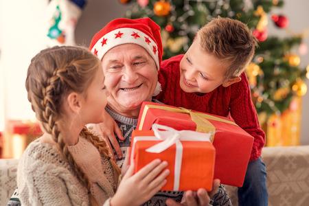 幸せな子供たちは、祖父からクリスマス プレゼントを受け取っています。自宅で座って、笑顔 写真素材 - 65153501