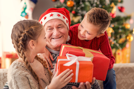Happy children are receiving Christmas gifts from grandfather. They are sitting at home and smiling Foto de archivo