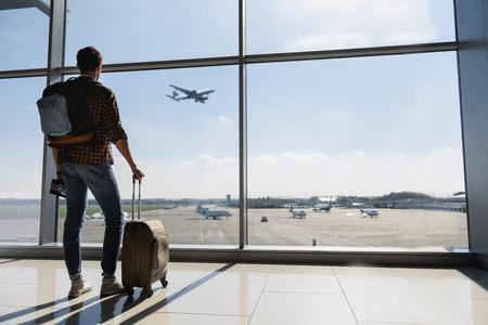 De jonge man staat dichtbij het raam bij de luchthaven en vliegt vliegtuig voor vertrek. Hij staat en draagt bagage. Focus op zijn rug