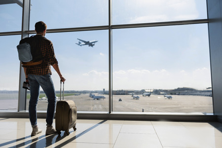 Young man is standing near window at the airport and watching plane before departure. He is standing and carrying luggage. Focus on his back