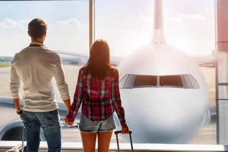 Adelante al futuro. Joven pareja amorosa está viendo avión aunque ventana antes de la salida. Están de pie en el aeropuerto y tomados de la mano Foto de archivo - 65153651