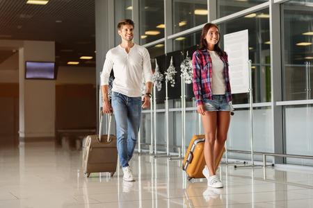 Felice giovane uomo e la donna sono in corso con i bagagli all'aeroporto. Non vedono l'ora di aspirazione e sorridente Archivio Fotografico - 65153832