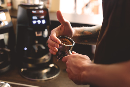 Barista, der oben einen gemahlenen Kaffee in einem portafilter, Abschluss, selektiven Fokus hält