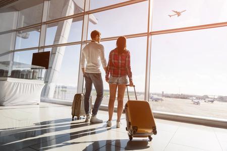 Nettes liebendes Paar beobachtet Flug und Sonnenuntergang am Flughafen. Sie stehen neben Fenster und tragen Koffer Standard-Bild - 65154718