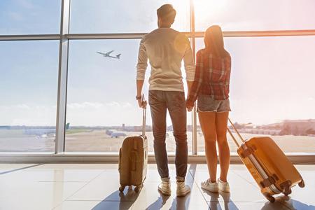 Het geïnspireerde jonge houdende van paar bekijkt vliegend vlakte in hemel. Ze staan vlakbij het raam op het vliegveld en houden elkaars hand vast