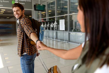 안녕. 젊은 여자는 공항에서 그녀의 남자 친구를보고있다. 그들은 손을 잡고 웃고있다 스톡 콘텐츠