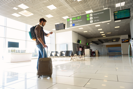 I am in time. Confident young man is looking at watch at airport with concentration. He is standing and carrying suitcase with backpack Imagens