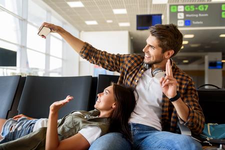 우리는 여행 할 준비가되어 있습니다. 행복 한 사랑의 커플 공항에서 셀키 만들기. 그들은 몸짓으로 웃고있다. 스톡 콘텐츠