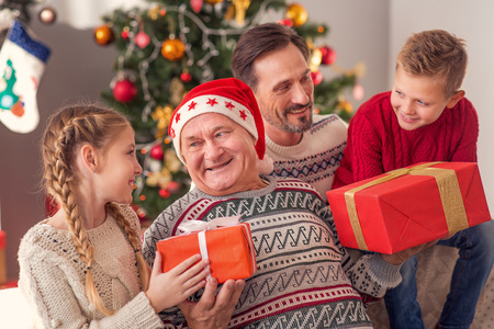 Happy Old Man Is Receiving Christmas Gifts From His Grandchildren ...