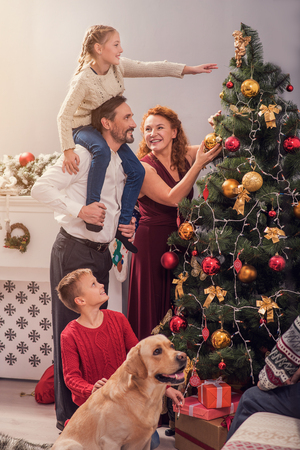 decorate: Joyful parents and children are hanging toys on Christmas tree. They are smiling with happiness