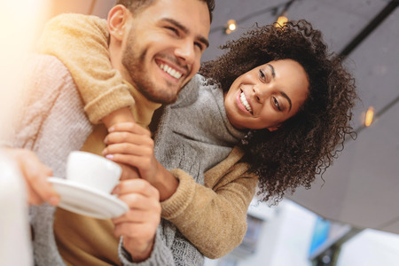 幸せなカップルの休憩、ハグとコーヒーを飲みながら笑みを浮かべて
