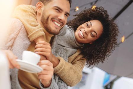 glückliches Paar ruht, umarmt und lächelt, während Kaffee zu trinken