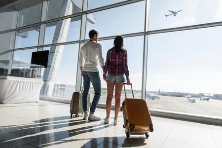 若い男性と女性は、夢見心地の空港で窓から探しています。荷物を運ぶ、手を繋いでいます。