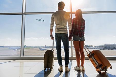 新しい未来への準備が整いました。若い男性と女性は、空港での飛行を見ています。立って、荷物を運ぶ