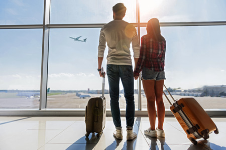 We are ready for new future. Young man and woman are watching flight at airport. They are standing and carrying luggage Archivio Fotografico