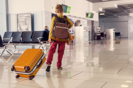 back gate: On way to his gate. Back view shot of little boy holding suitcase and walking down hall of airport Stock Photo