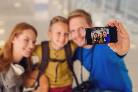 say cheese: Say cheese. Close up of happy smiling family making selfie, using smartphone while staing at airport