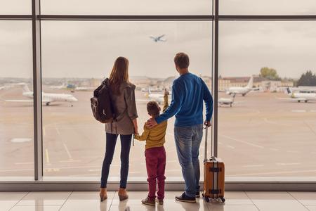 그런 대형 항공기. 탑승하기 전에 공항 창문 근처에 서있는 수하물로 젊은 가족의 다시보기 샷