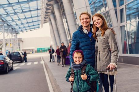 Organizado y listo para funcionar. Recortar foto de la familia feliz que se coloca cerca de la entrada exterior del aeropuerto y en espera de la llegada del taxi