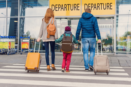 We are ready to fly. Rear view of young family travelling in international airport and holding suitcases in their hands