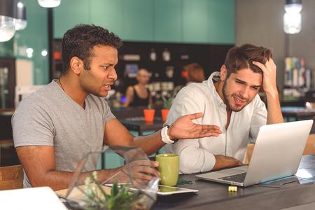 Ich versteh nichts. Shot von ärgerlichen männlichen Studenten sitzen und reden vor dem Unterricht im Café Standard-Bild - 65356071