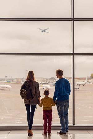 ほぼ、当社のフライトの時間。親のビュー ショットと面の大きな窓の外を見て、空港に着陸を待っている子供たち 写真素材 - 65356094
