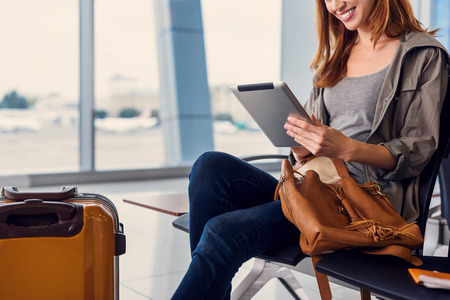 cropped out: Checking out latest posts. Cropped photo of attractive young woman holding digital tablet at airport while waiting for her flight