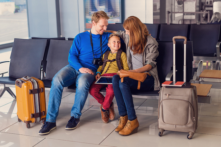 cheerfully: Family is little world created by love. Beautiful family at airport before boarding, sitting in waiting hall and cheerfully smiling Stock Photo