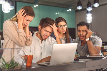 buddies: Brainstorming buddies. Photo of stressed students looking at laptop screen during sitting in cafe Stock Photo